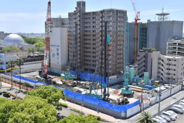 2020年秋の開業に向けて工事が進む駅前ビルの建設現場=21日午前