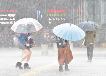 激しい風雨に身をかがめ、駅に向かう人たち=21日午後1時37分、JR水戸駅、吉田雅宏撮影