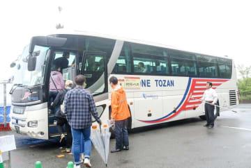 雨が降りしきる中、箱根ロープウェイの代行バスに乗り込む観光客ら=21日午後、早雲山駅前
