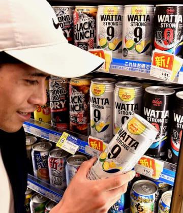 オリオン缶チューハイ「WATTA」を手に取る観光客=那覇市・ファミリーマートレグザリウボウ店