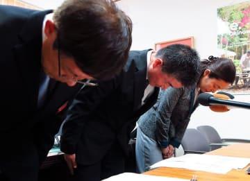 記者会見で謝罪する沖縄県の新垣健一文化観光スポーツ部長(中央)ら=21日、沖縄県庁