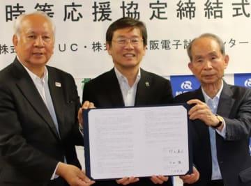 【協定書を示す(左から)小山社長、竹上市長、久田会長=松阪市役所で】