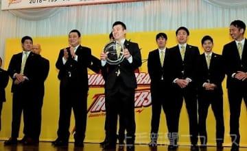 関係者を前に、東地区優勝の記念プレートを持つ佐藤主将(中央)ら