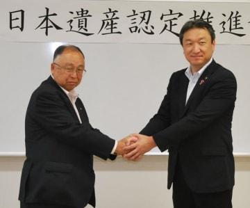 鋸山の日本遺産認定を目指し握手する高橋市長(右)と白石町長=21日、富津市
