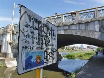 落書きされた鴨川河川敷の看板(京都市東山区・七条大橋東詰)
