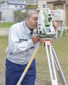 機器を使い、グラウンドを測量するサポートプランニングの社員