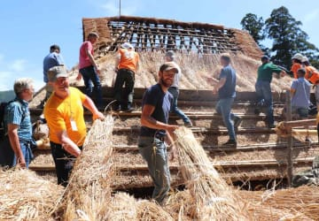 かやぶき屋根のかや敷きを体験した海外からの参加者(南丹市美山町北)