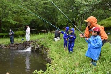 雨の中、かっぱを着込んで釣り糸を垂れる「三股町ヤマメ釣り大会」の参加者