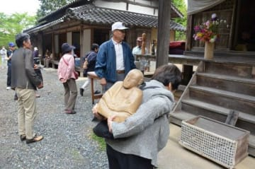 仏像を背負い、薬師堂の周囲を3周する参拝客=12日