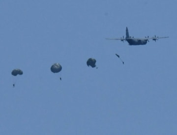 MC130特殊作戦機からパラシュートで降下する4人の兵士=22日午後1時ごろ、うるま市・津堅島訓練場水域