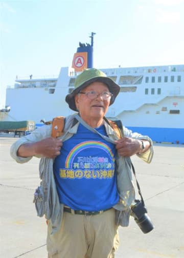 「基地のない沖縄を」Tシャツを示しながら沖縄路の意気込みを話す石川文洋さん=22日、本部港