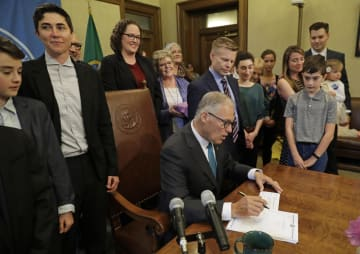 関係者らが見守る中、法案に署名する米ワシントン州のインズリー知事(中央)=21日、ワシントン州オリンピア(AP=共同)