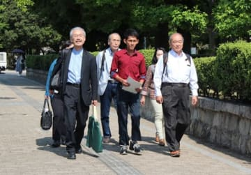 日本語能力が足りないことを理由に不当に帰国させられたとして、提訴のため広島地裁に向かうリキさん(手前中央)