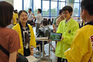 村の法被などを羽織り、買い物客(左端)に笑顔で田んぼアートをPRする田舎館中生たち=東京・台場