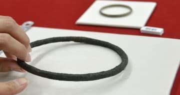 下鈎遺跡で出土したリング状の青銅品。分銅の可能性が高いことが分かった。奥は腕輪の「銅釧」=滋賀県栗東市