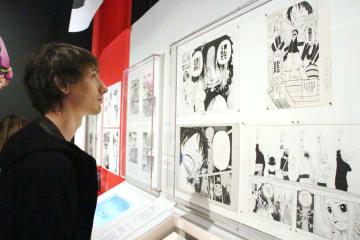 大英博物館の「漫画展」で展示された原画を見る来場者=23日、ロンドン(共同)