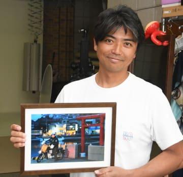 夕暮れ時の三崎港で撮影した愛車写真を手に、サービスをPRする三上さん=三浦市三崎