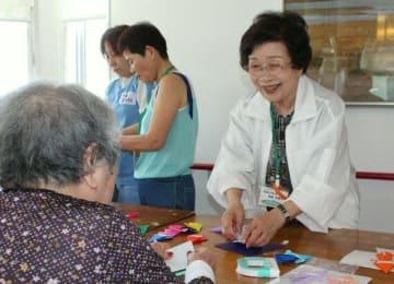 奉仕活動の一環で、わさだケアセンターの折り紙クラブで入所者に折り方を教えるナルク大分の会員=大分市市