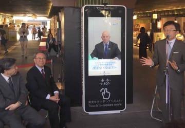 リニューアルした最新のデジタルサイネージの機能を使って東京からあいさつするウェスト社長(画面)=京都市右京区・嵐電嵐山駅