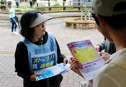 道行く若者らにチラシを配る過労死遺族の西垣迪世さん=神戸市中央区
