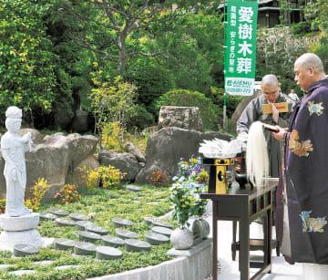 保善院内の「いずみの郷ゆがわら樹木葬墓地」で合同法要を執り行う西有善裕住職(右)