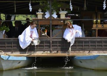 大分県日田市の「日田川開き観光祭」で、みこに扮しアユを放流する女性=25日午前
