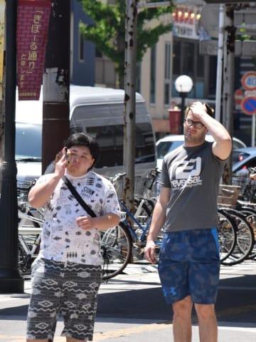 強い日差しが照りつける中、汗をタオルでぬぐったり手で日差しを遮ったりする通行人=24日午後、千葉市中央区