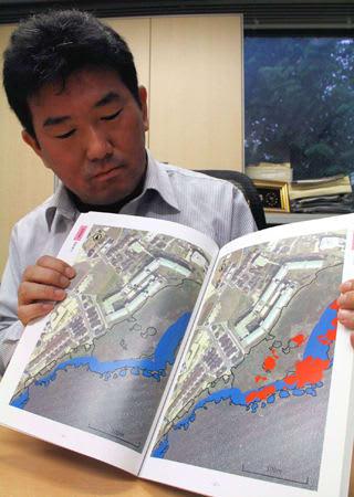 オオバナミズキンバイが繁殖する可能性が高い地点を青く塗ったマップを持つ田中准教授。赤い部分は2016年に生息を確認した区域(京都市左京区・京都大)