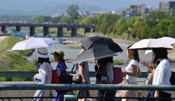 強い日差しの下、日傘を差して歩く人たち(25日午後3時11分、京都市・四条大橋)
