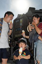 真夏を思わせる暑さの中、アイスクリームを食べる親子=25日午後、神戸市中央区元町通1、南京町広場(撮影・後藤亮平)