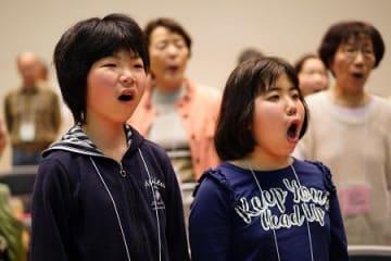大人と一緒に練習に励む堤さん(手前左)と原内さん(手前右)=鳴門市文化会館