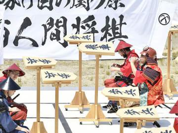 夏を思わせる暑さの中であった「東西人間将棋」で、対局の合間に水分を補給する人間駒の男性=25日午後0時30分、不破郡関ケ原町、笹尾山グラウンド