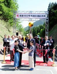 国道482号の供用開始を祝い、県境で握手を交わした井戸敏三兵庫県知事(左)と野川聡鳥取県副知事