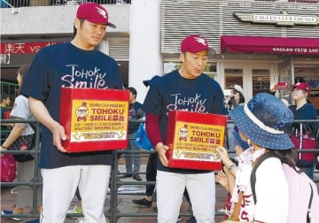 試合に訪れたファンから寄付を集める塩見選手(左)と美馬選手