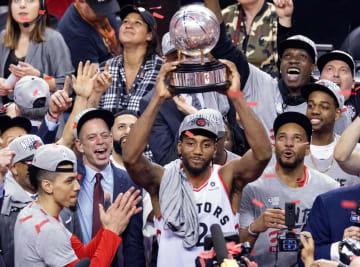 NBA決勝進出を決め、トロフィーを掲げて喜ぶラプターズのレナード(中央)=トロント(カナディアンプレス提供・AP=共同)