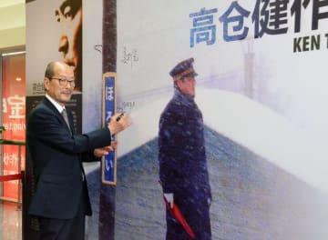 中国上海市の映画館に設置された高倉健さん主演の「鉄道員(ぽっぽや)」のパネルにサインする降旗康男監督=2015年6月(共同)