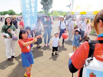 熱中症対策キーパーが噴霧するミストを浴びて涼む子どもたち=26日午後、熊谷市上川上の熊谷スポーツ文化公園
