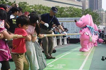 大会マスコット「スフラ」が参加して繰り広げられた綱引き=26日、大阪市北区のグランフロント大阪うめきた広場