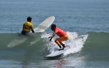 サーフィンの技を競う選手=26日、いすみ市