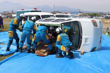 横転した車両から負傷者を救出する訓練に臨む関係者=雲仙市、多比良港埋め立て地