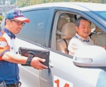 スタッフの指導で運転能力を確かめる参加者(右)=26日、大分市賀来北の県自動車学校
