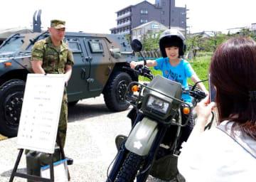 陸上自衛隊の偵察用オートバイに乗って記念撮影をする来場者(京都府京丹後市網野町・八丁浜シーサイドパーク)
