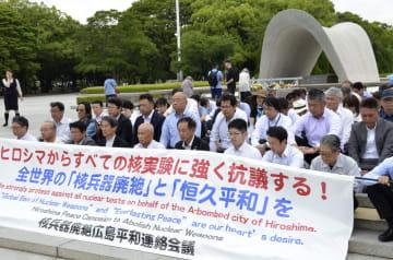 米核研究機関が臨界前核実験を実施したことを受け、抗議の座り込みを行う人たち=27日、広島市の平和記念公園