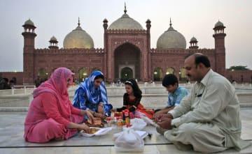 パキスタンで21日、ラマダン初日の日の入り後、食事を共にする家族(AP=共同)
