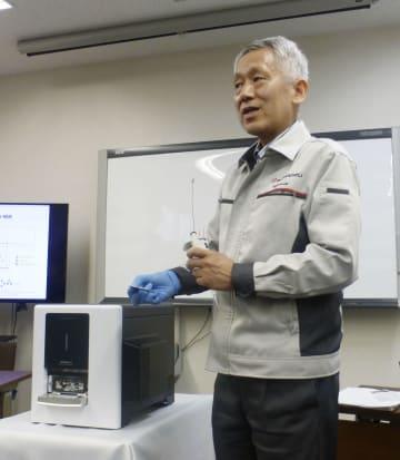 世界最小の卓上型質量分析計(左下)の発売を発表する島津製作所の田中耕一氏=28日、京都市
