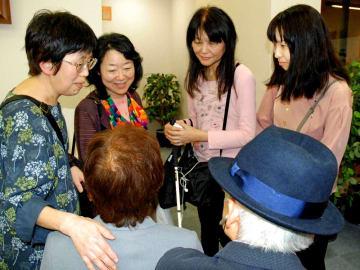 報告集会の後、原告の飯塚さん(手前左)を囲む利光さん(左端)や横川さん(右端)=仙台市・仙台弁護士会館
