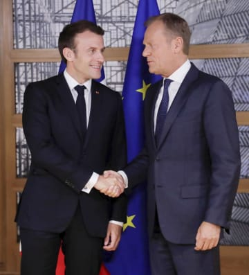 握手を交わす欧州連合のトゥスク大統領(右)とフランスのマクロン大統領=28日、ブリュッセル(ロイター=共同)