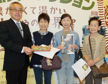吉岡社長(左)から記念品を贈られる小川さん(左から2人目)=28日、米子市美術館
