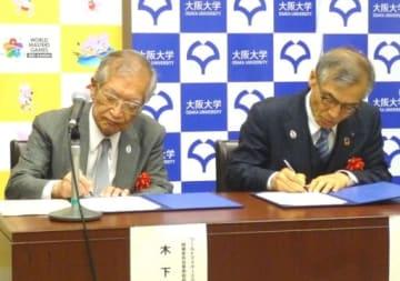 協定書にサインをする関西組織委の木下事務総長(左)と阪大の西尾総長=28日、大阪市北区