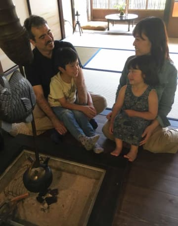 イタリアから夫と共に出身地の亀岡市に戻り、ゲストハウスを開いた川本さん(右)。夫と2人の子どもと楽しく暮らす=京都府亀岡市千歳町